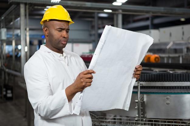 Männlicher arbeiter, der anweisungen an der saftfabrik liest