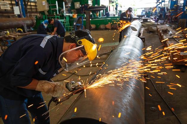 Männlicher arbeiter, der auf stahlplatte mit funkenblitz schleift, nahaufnahme schutzhandschuhe tragen