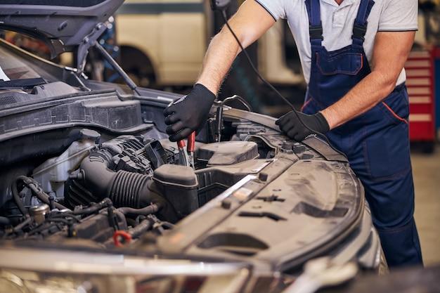 Männlicher arbeiter, der auto an der reparaturservicestation repariert