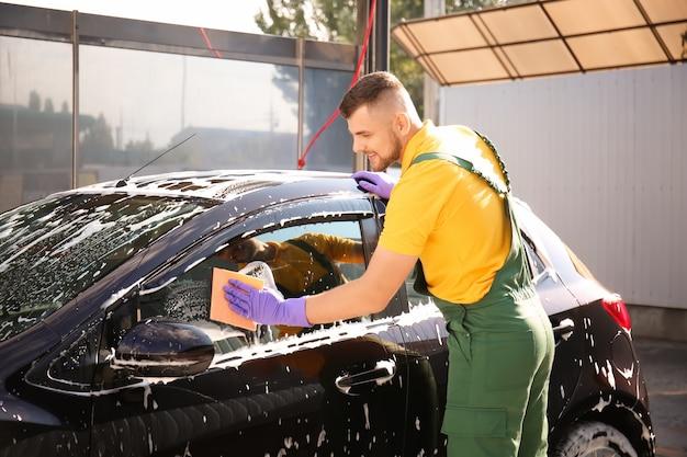 Männlicher arbeiter, der auto im freien wäscht