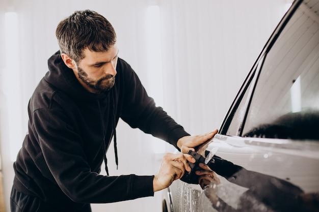 Männlicher arbeiter, der auto mit schutzfolie einwickelt