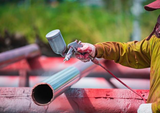 Männlicher arbeiter, der eine spritzpistole in industriegröße hält, die für die pipeline-oberfläche auf der industriellen stahllackierung und -beschichtung verwendet wird.