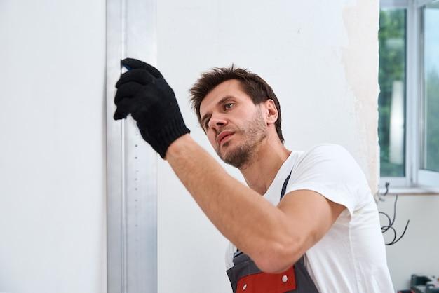 Männlicher arbeiter, der eine wand unter verwendung eines langen spatels verputzt. renovierungskonzept