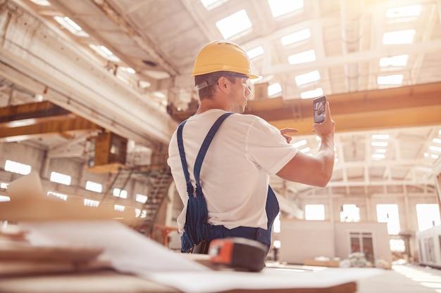 Männlicher arbeiter, der gebäudefoto mit modernem smartphone macht