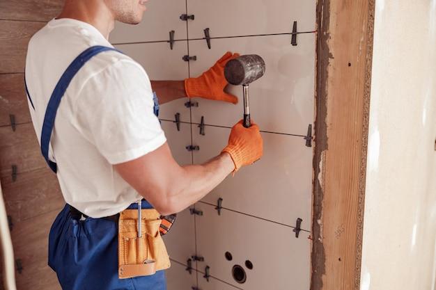 Männlicher arbeiter, der keramische wandfliesen im haus anbringt
