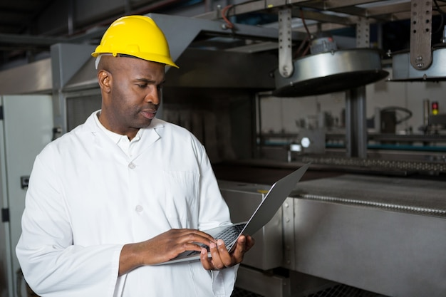 Männlicher arbeiter, der laborkittel trägt, während laptop in saftfabrik verwendet