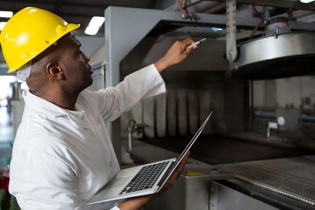 Männlicher arbeiter, der laborkittel trägt, während laptop verwendet wird