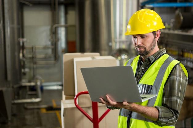 Männlicher arbeiter, der laptop im verteilungslager verwendet