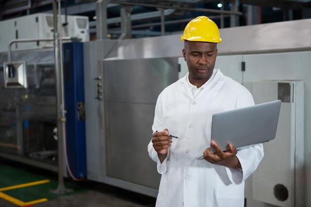 Männlicher arbeiter, der laptop in der fertigungsindustrie verwendet