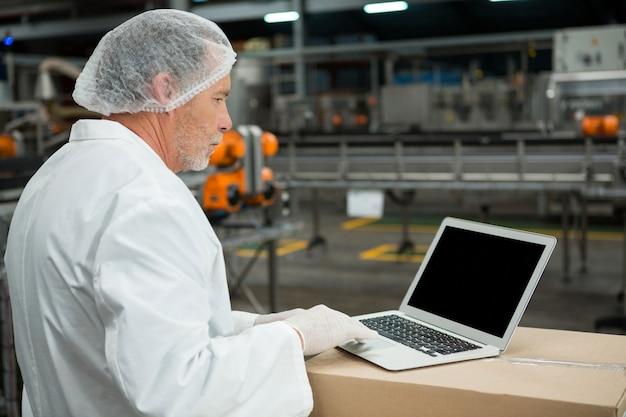 Männlicher arbeiter, der laptop in fabrik verwendet