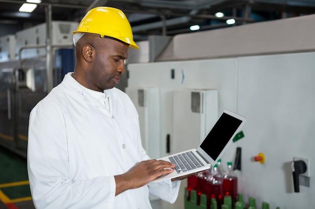 Männlicher arbeiter, der laptop in saftfabrik verwendet