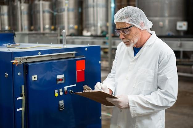 Männlicher arbeiter, der maschinen an der kaltgetränkefabrik inspiziert