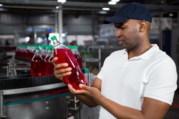 Männlicher arbeiter, der saftflasche in der fabrik inspiziert