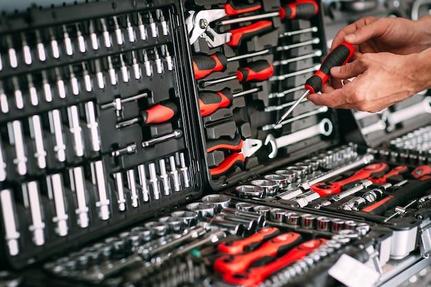Männlicher arbeiter, der schraubendreher im werkzeugspeicher wählt