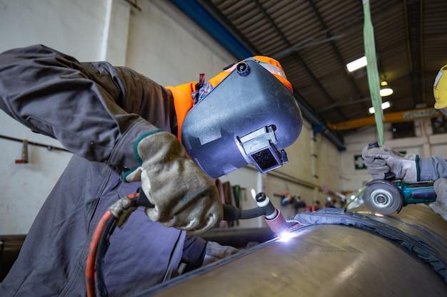 Männlicher arbeiter, der schutzkleidung des rostfreien argonschweißens des reparaturrohres des industriebaus trägt