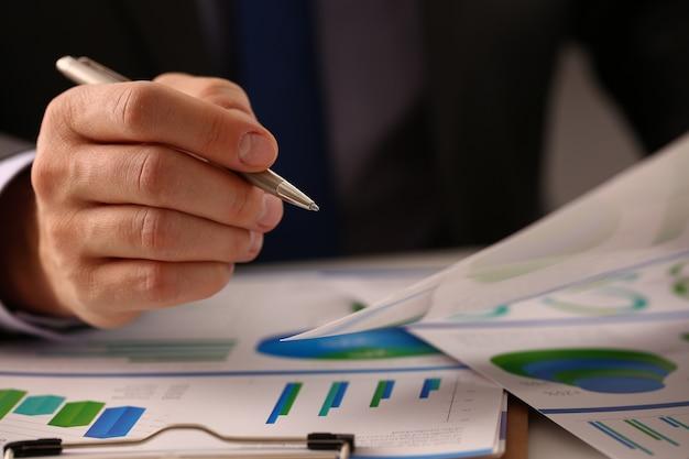 Männlicher arbeiter, der statistikbericht bei der arbeit analysiert