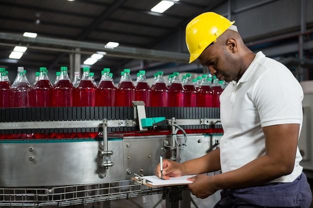 Männlicher arbeiter, der über produkte in der fabrik bemerkt