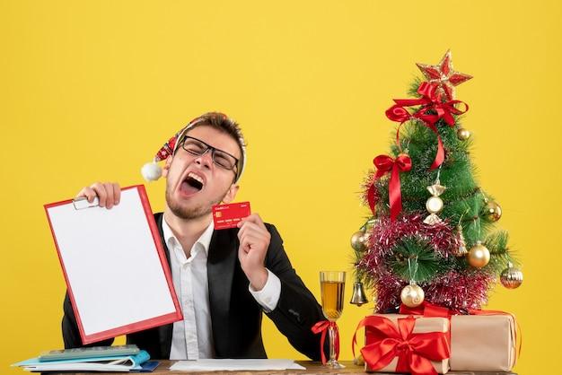 Männlicher arbeiter der vorderansicht, der bankkarte und notiz um kleinen weihnachtsbaum hält und gähnen auf gelb präsentiert