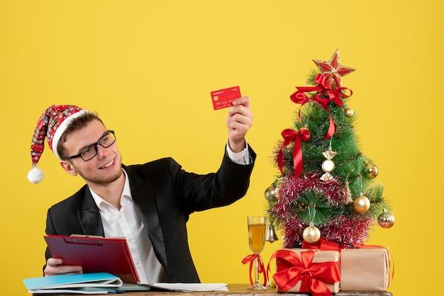 Männlicher arbeiter der vorderansicht, der bankkarte und notiz um kleinen weihnachtsbaum und geschenke auf gelb hält