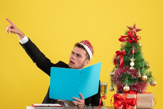 Männlicher arbeiter der vorderansicht, der dokumente auf gelb sitzt und hält
