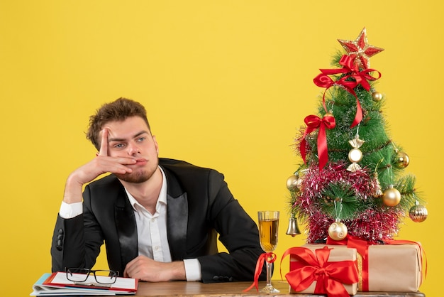 Männlicher arbeiter der vorderansicht, der hinter seinem arbeitsplatz auf gelb sitzt