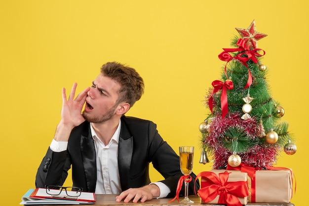 Männlicher arbeiter der vorderansicht, der hinter seinem arbeitsplatz sitzt und gelb anruft
