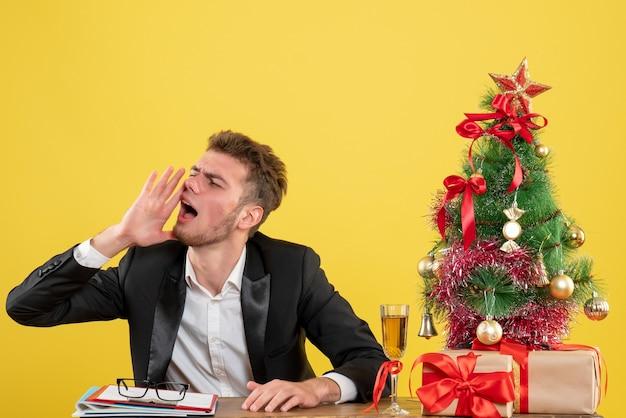 Männlicher arbeiter der vorderansicht, der hinter seinem arbeitsplatz sitzt und jemanden auf gelb ruft