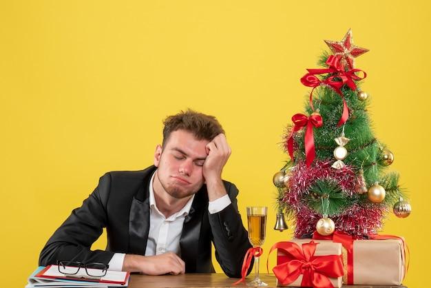 Männlicher arbeiter der vorderansicht, der hinter seinem arbeitsplatz sitzt und sich auf gelb müde fühlt