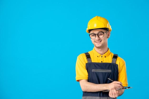 Männlicher arbeiter der vorderansicht in der gelben uniform, die notizen auf blau macht