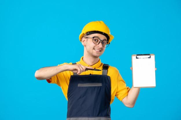 Männlicher arbeiter der vorderansicht in der gelben uniform mit aktennotiz auf blau