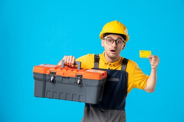 Männlicher arbeiter der vorderansicht in der gelben uniform mit werkzeugkasten und kreditkarte auf blau