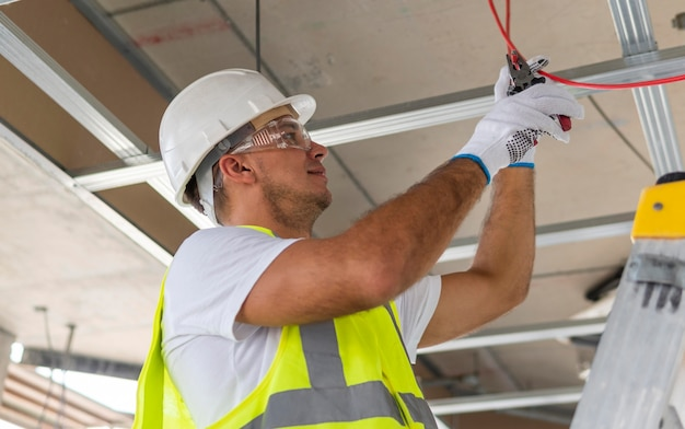 Männlicher arbeiter im bau, der schutzausrüstung trägt
