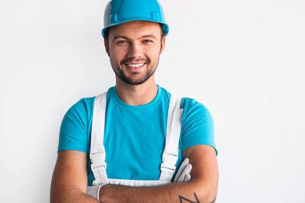 Männlicher arbeiter im helm über weißer wand