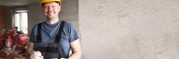 Männlicher arbeiter im schutzhelm und im overall