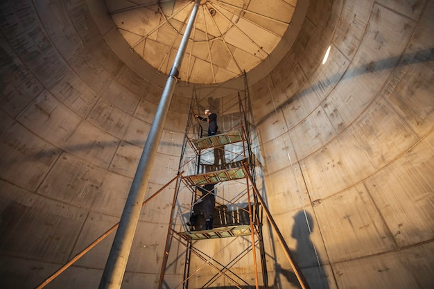 Männlicher arbeiter in arbeit tank edelstahl-inspektionsgerüst auf engstem raum