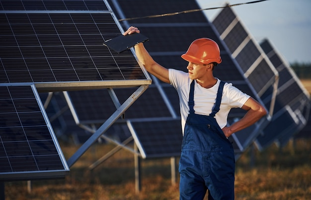 Männlicher arbeiter in blauer uniform im freien mit solarbatterien am sonnigen tag.