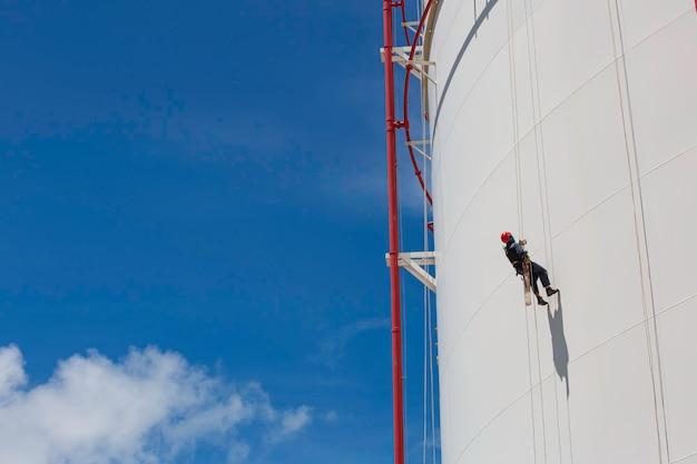 Männlicher arbeiter in der höhe der tankoberteilplatte seilleiter zugangssicherheitsinspektion des dickenspeichertanks propangas.