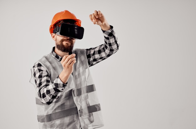 Männlicher arbeiter in einem orangefarbenen helmtechnologie-profi isolierten hintergrund