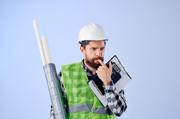 Männlicher arbeiter in einem weißen helm blaupausen professioneller blauer hintergrund. foto in hoher qualität