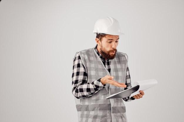 Männlicher arbeiter in einem weißen helm blaupausen professioneller isolierter hintergrund