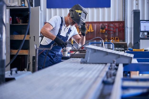 Männlicher arbeiter in handschuhen, der die schutzmaske abnimmt, während er den schweißbrenner hält