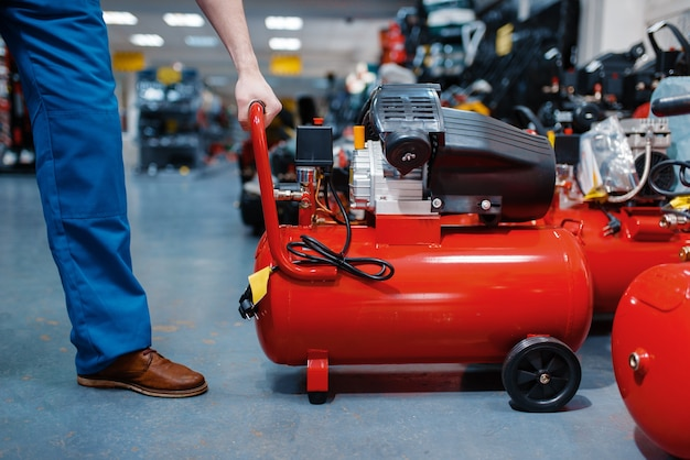 Männlicher arbeiter in uniform, der einen pneumatischen kompressor im werkzeugladen wählt
