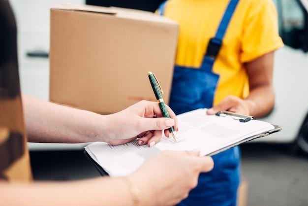 Männlicher arbeiter in uniform gibt dem kunden ein paket, vertriebsgeschäft. frachtlieferung.