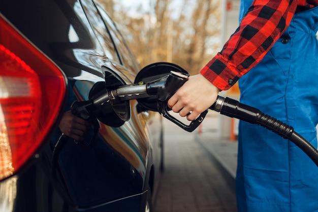 Männlicher arbeiter in uniform kraftstofffahrzeug an tankstelle, kraftstoffbefüllung. benzintanken, benzin- oder dieseltankservice