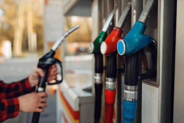 Männlicher arbeiter in uniform nimmt eine waffe an einer tankstelle, tankfüllung. benzintanken, benzin- oder dieseltankservice