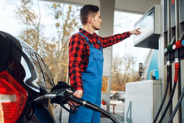 Männlicher arbeiter in uniform tankt auto an tankstelle, tankfüllung. benzintanken, benzin- oder dieseltankservice