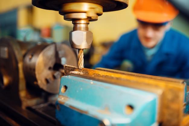 Männlicher arbeiter in uniform und helm arbeitet an der nahaufnahme der drehbank, anlage. industrielle produktion, metalltechnik, herstellung von kraftmaschinen