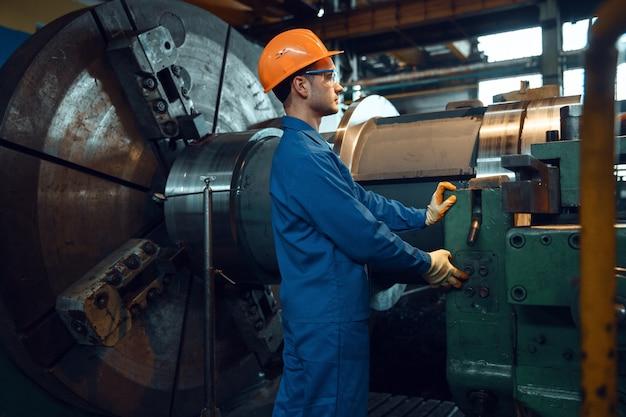 Männlicher arbeiter in uniform und helm beginnt drehmaschine in der fabrik