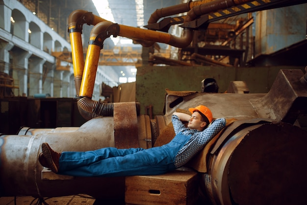 Männlicher arbeiter in uniform und helm, die zur mittagszeit in der fabrik ruhen. metallverarbeitende industrie, industrielle herstellung von stahlprodukten