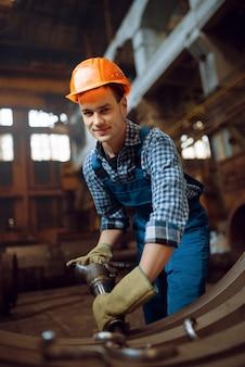 Männlicher arbeiter in uniform und helm entfernt ab werk schuppen von metallwerkstücken. metallverarbeitende industrie, industrielle herstellung von stahlprodukten